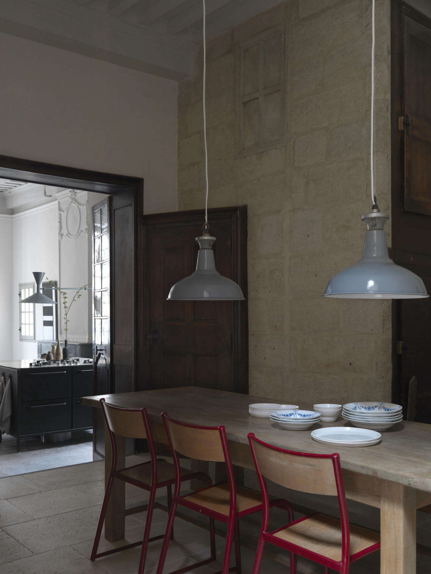In the dining room, vintage school chairs surround an oak dining table. The  industrial pendant lights are from Chris&#8