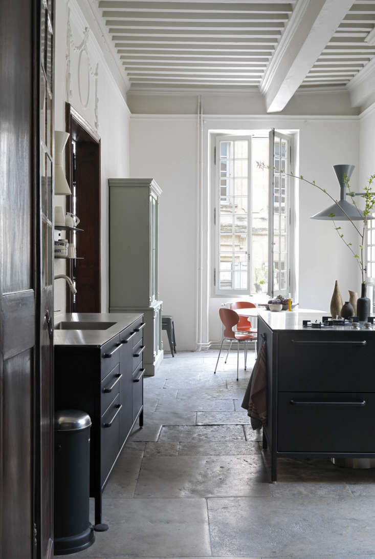 Second Act A London Design Couples Townhouse in a Small French Market Town A vintage painted hutch offers a warm contrast in the kitchen. Note the \13 foot high ceiling.