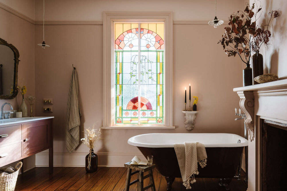 A soothing bath features original floorboards—and a stained-glass window.