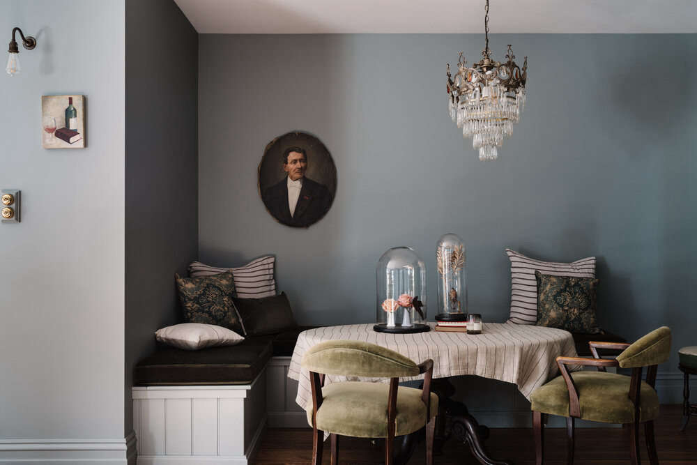 The dining nook is fitted with built-in banquettes and mossy velvet cushions.