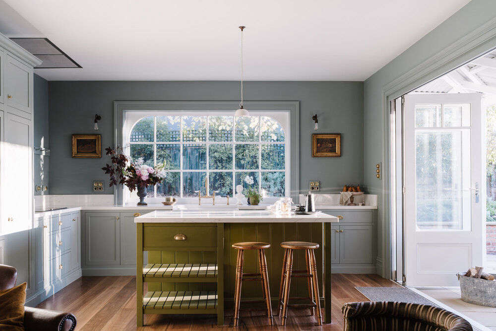 The English-style kitchen is fitted with Neff appliances and a farmhouse sink that overlooks the cottage garden.