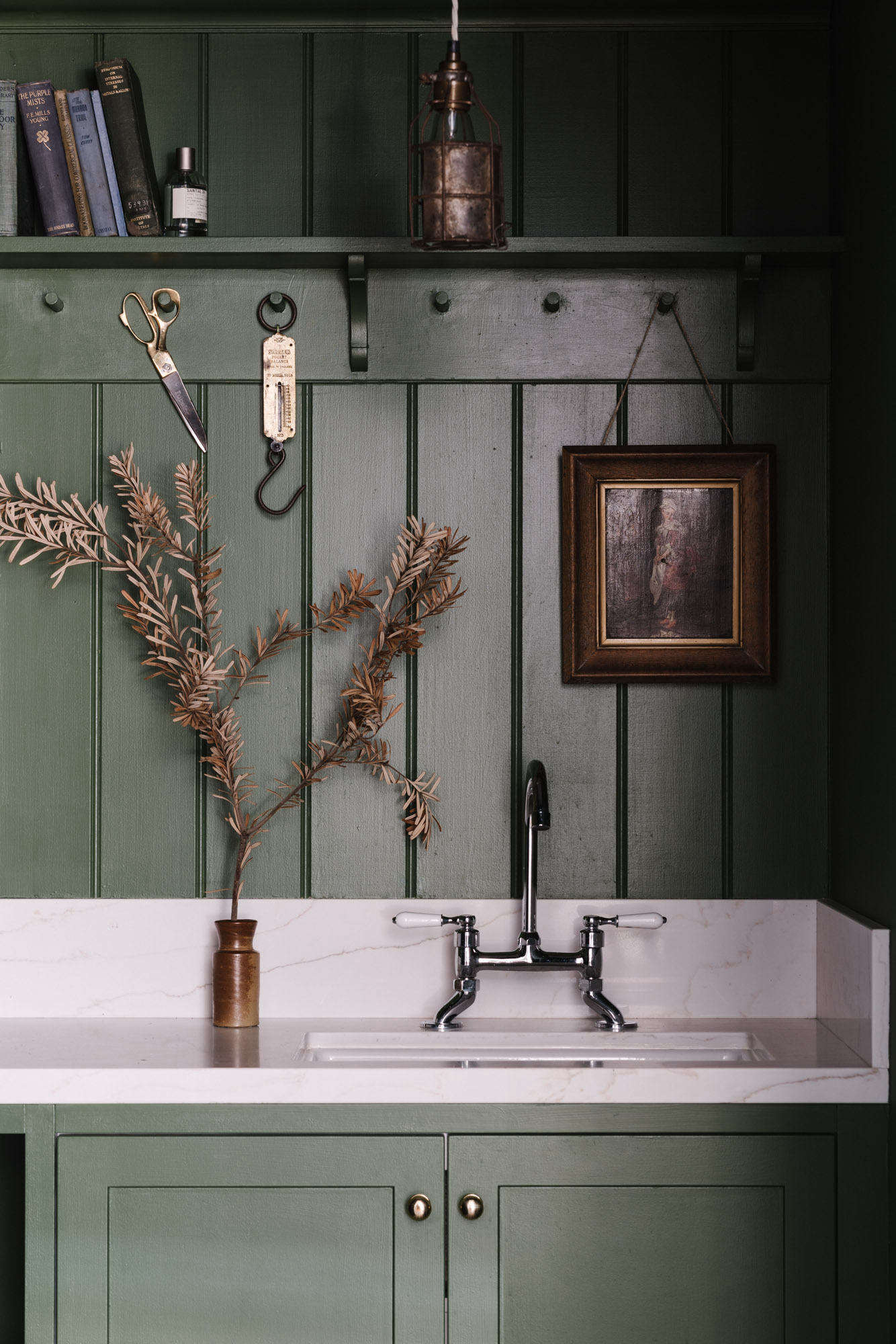 The postage stamp-sized room is fitted with peg rails and custom cabinetry painted in deep Green Velvet by Porter&#8
