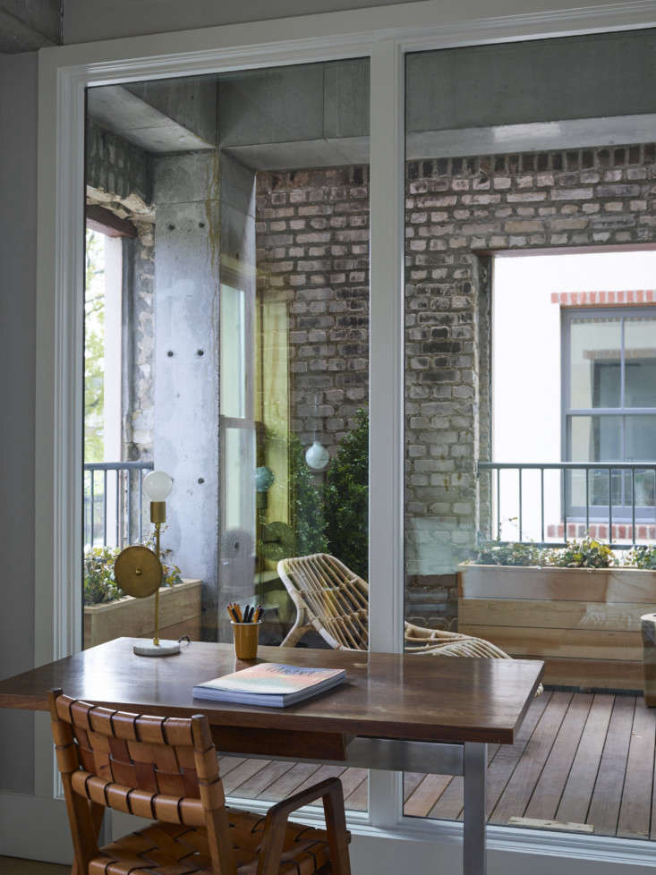 A glass wall on the office end of the room overlooks the open-air balcony with exposed brick and cedar planters.