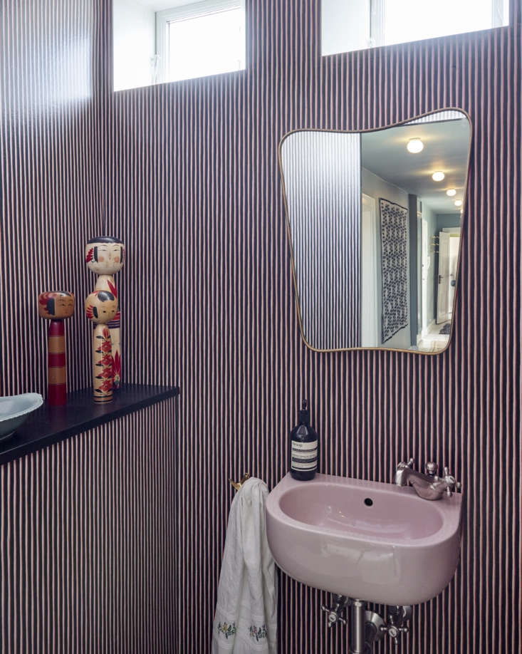 The pretty-in-pink powder room. The Painted Stripe wallpaper—black, orange, and pink—is another Tapet Cafe design. The Brass Mirror is a Gio Ponti classic from the 50s available from The Apartment (&#8