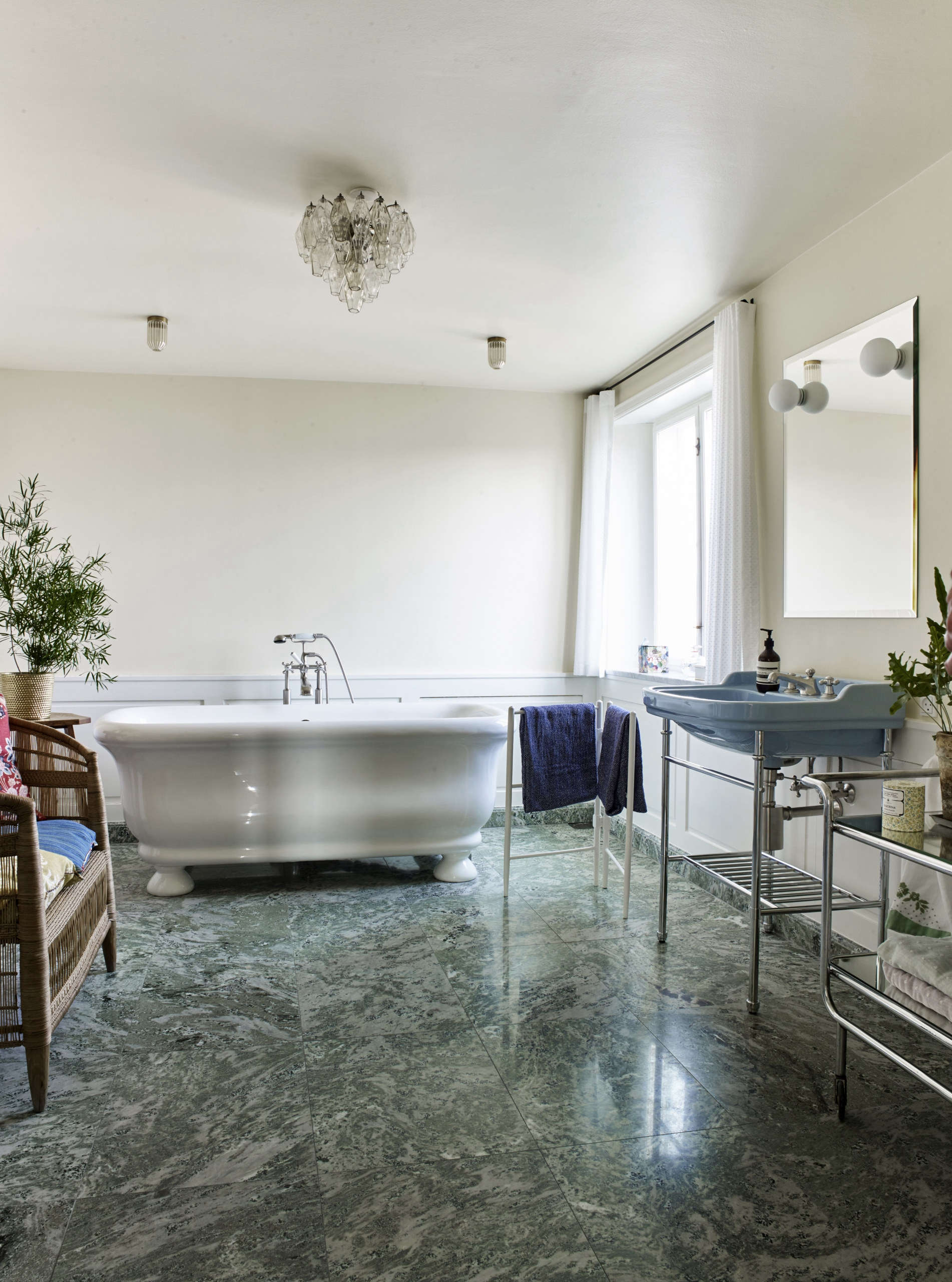 The bathroom has a Swedish green marble floor and a freestanding tub. A 50s French Bar Cart serves as storage shelves.