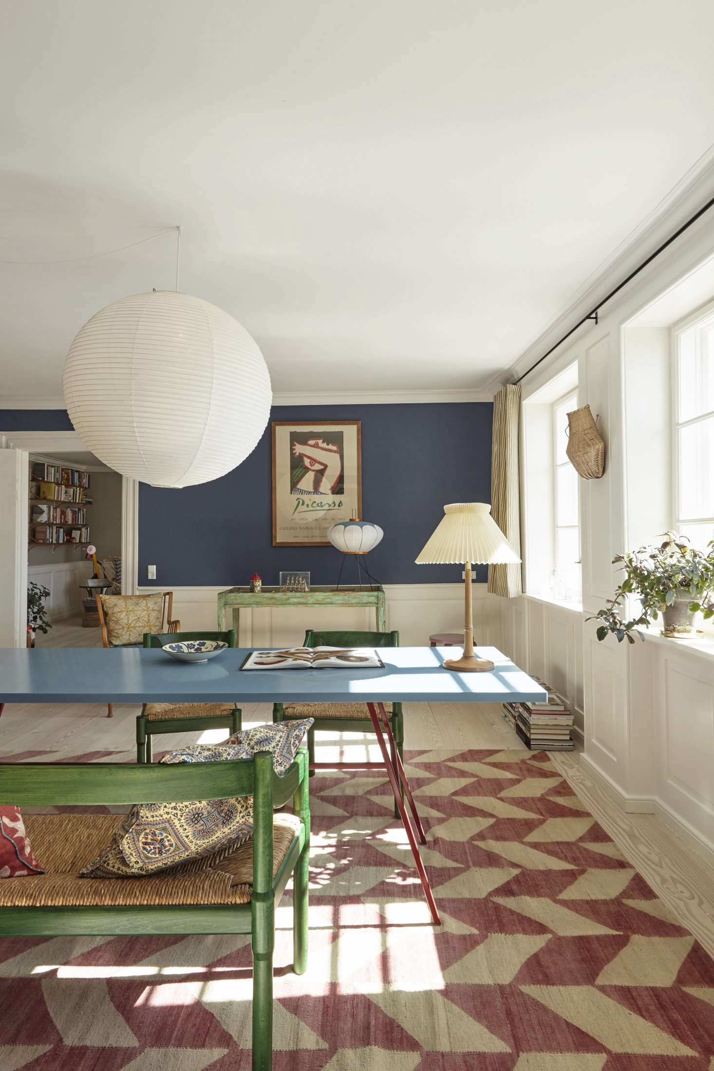The blue on the walls is Farrow & Ball Drawing Room Blue. The dining chairs are a Vico Magistretti design from 59.