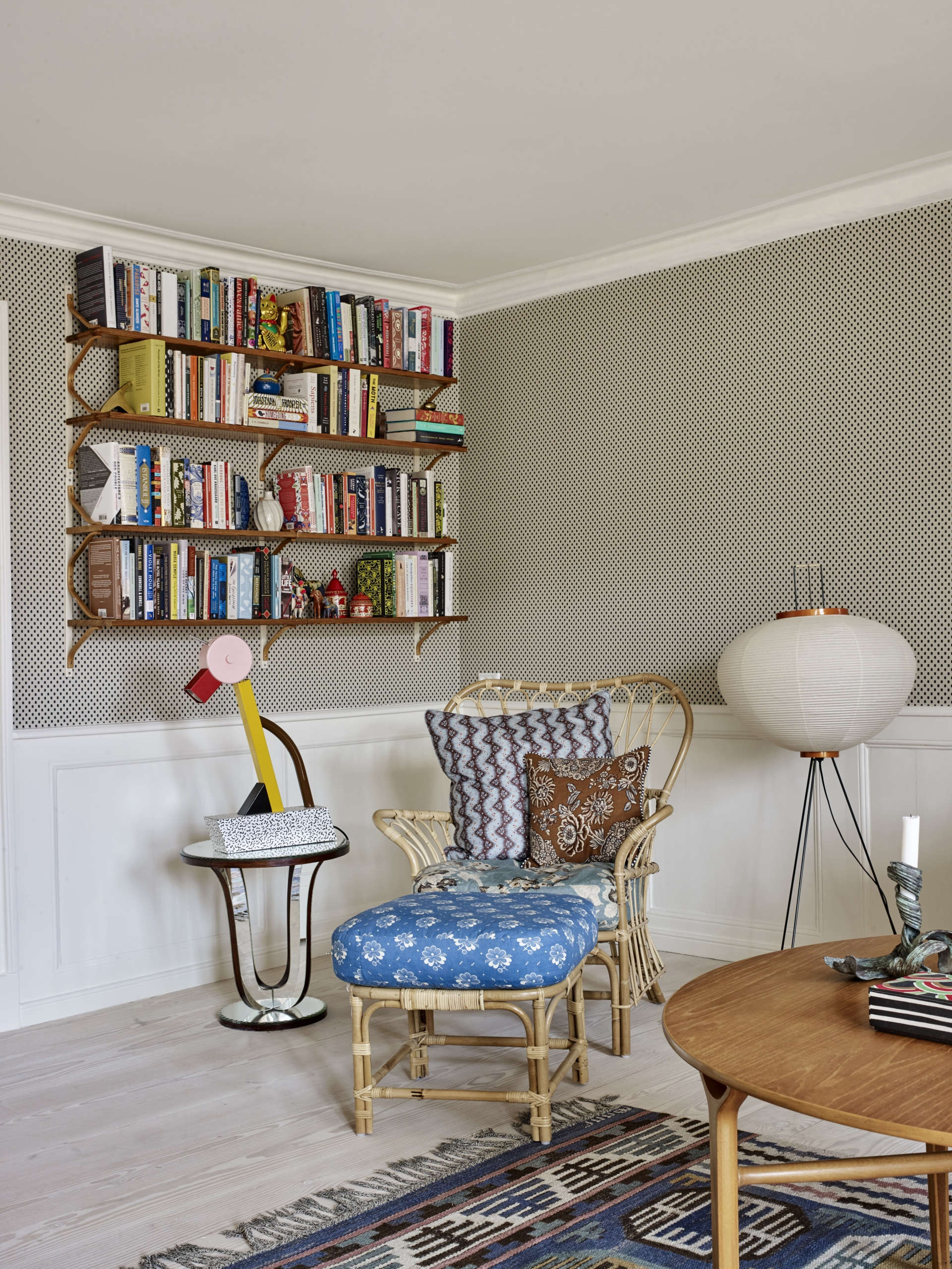 In the library corner of the room, Tina layered patterns on a rattan chair and paired it with Ettore Sottsass&#8