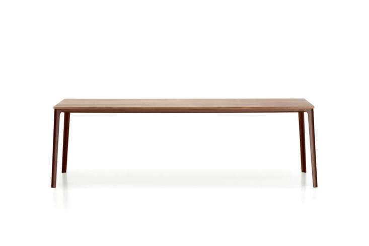 The Vitra Plate Dining Table features an oak (shown), Carrara marble, or satin-finished glass with a powder coated base in chocolate, white, or Earth Grey; prices starting at $3,4 from Connox.