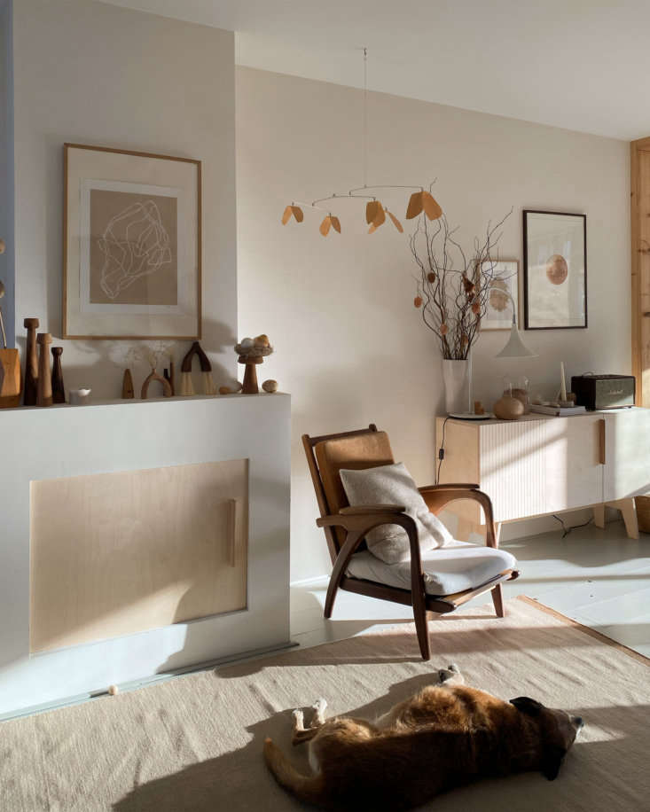 Their dog, Paxi, lounges in a stream of sunshine. The wooden mobile is by Bookhou.