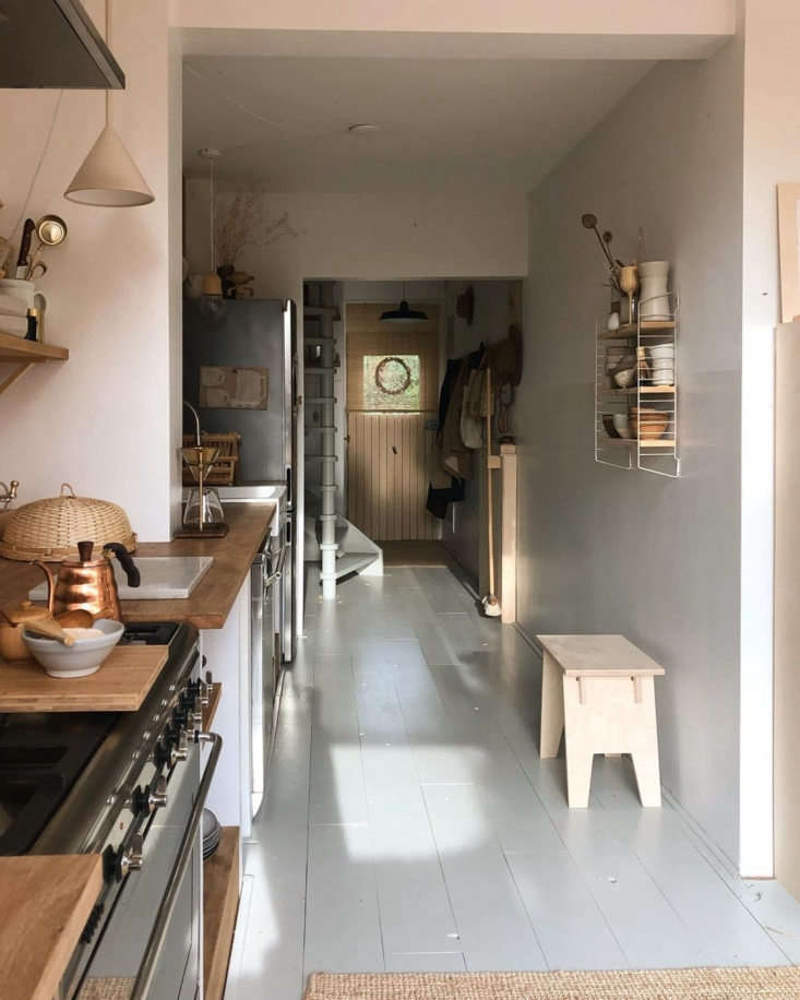 A galley-esque kitchen is just off the entry. Their Haru Stool sits under wall shelving by String.