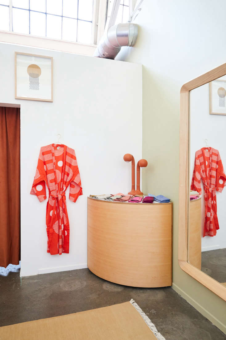 The Sidewinder Robe hangs next to a display of Table Linens (napkins are $ each).