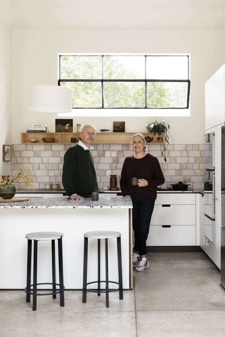 The couple in their new kitchen. The concrete floors from their former kitchen were simply cleaned up and polished. The stools are by Tait.