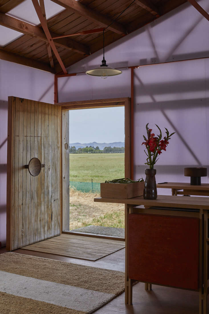 Ben made the paneled front door from parts of an old stable door of solid rimu wood. He carved the outsized handle from &#8