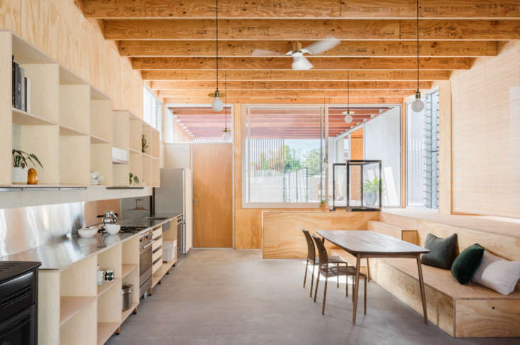 The living happens on the second level, above the carport and entry courtyard. A simple kitchen with plywood built-ins and stainless steel countertops greets visitors. From the architect&#8