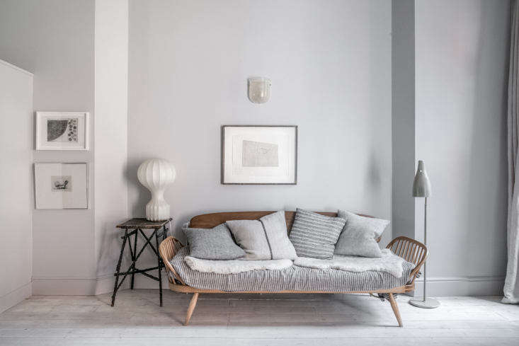The home is decorated with a mix of custom designs, contemporary pieces, and vintage finds—like the Ercol sofa and the &#8