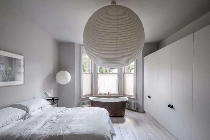 More Noguchi pendants in the master bedroom, which features a French cast-iron bathtub, found on eBay, in front of bay windows. There&#8