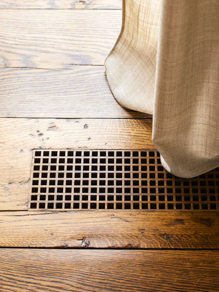 All in the details: reclaimed oak floors with a custom wood grate. Photo by Eric Piasecki.