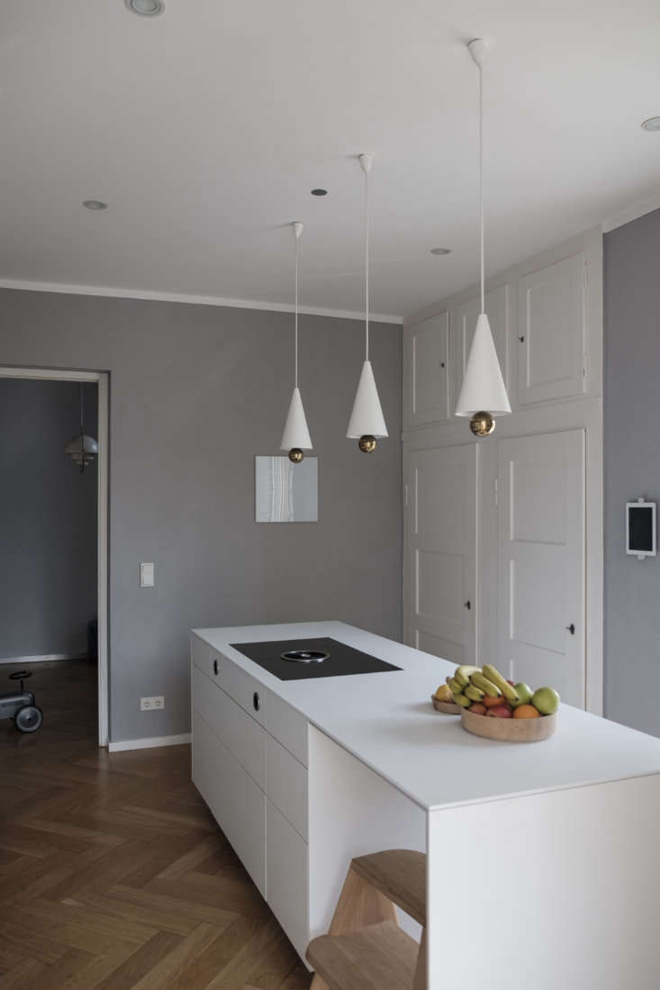 The family replaced the existing kitchen island with a sleeker, fully loaded Bulthaup design. Studio Oink paired it with Cherry pendant lights from Petite Friture and kept the existing gray walls and built-in cabinets, newly enlarged some to fit a microwave and Brita water station.