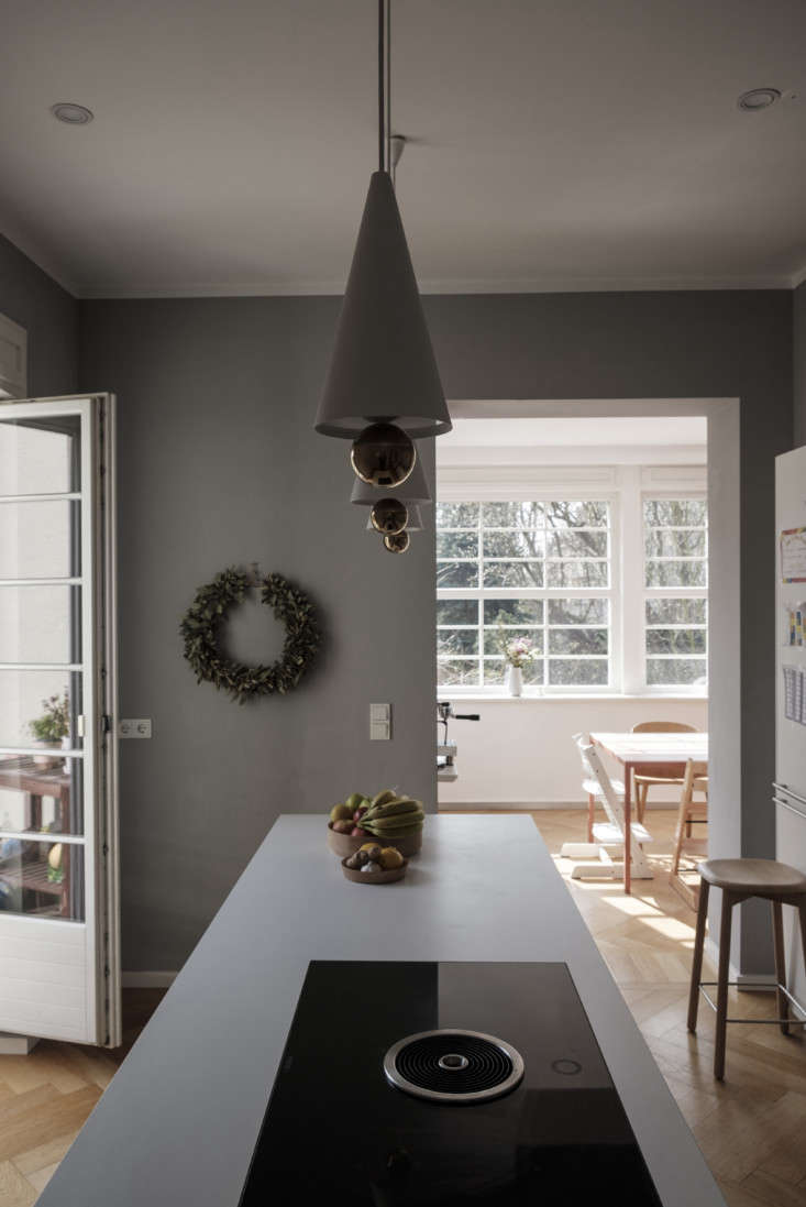 The fridge is in a corner of the room that opens to the dining area. Accordion doors lead to the garden.