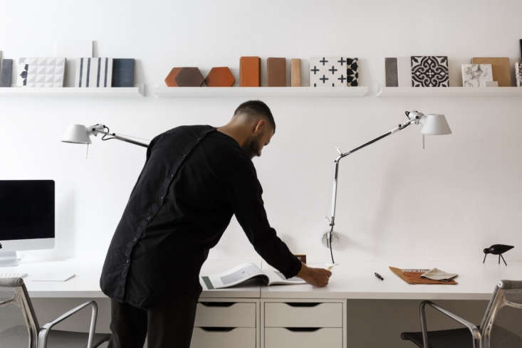 michael in front of simple built in desks and a display of tile samples. under  12