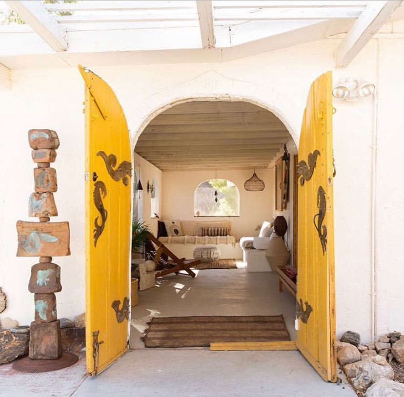 The sunny yellow front doors are original to the 50s Spanish-style ranch house.
