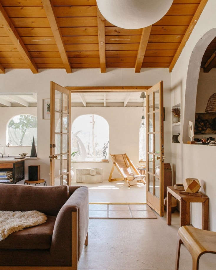 Merchant House High Desert A SpanishStyle Oasis in the Mojave French doors lead to the living room. Denise and Sara painted the plaster walls and concrete floor white. The arched window to the right affords a peek into the kitchen.