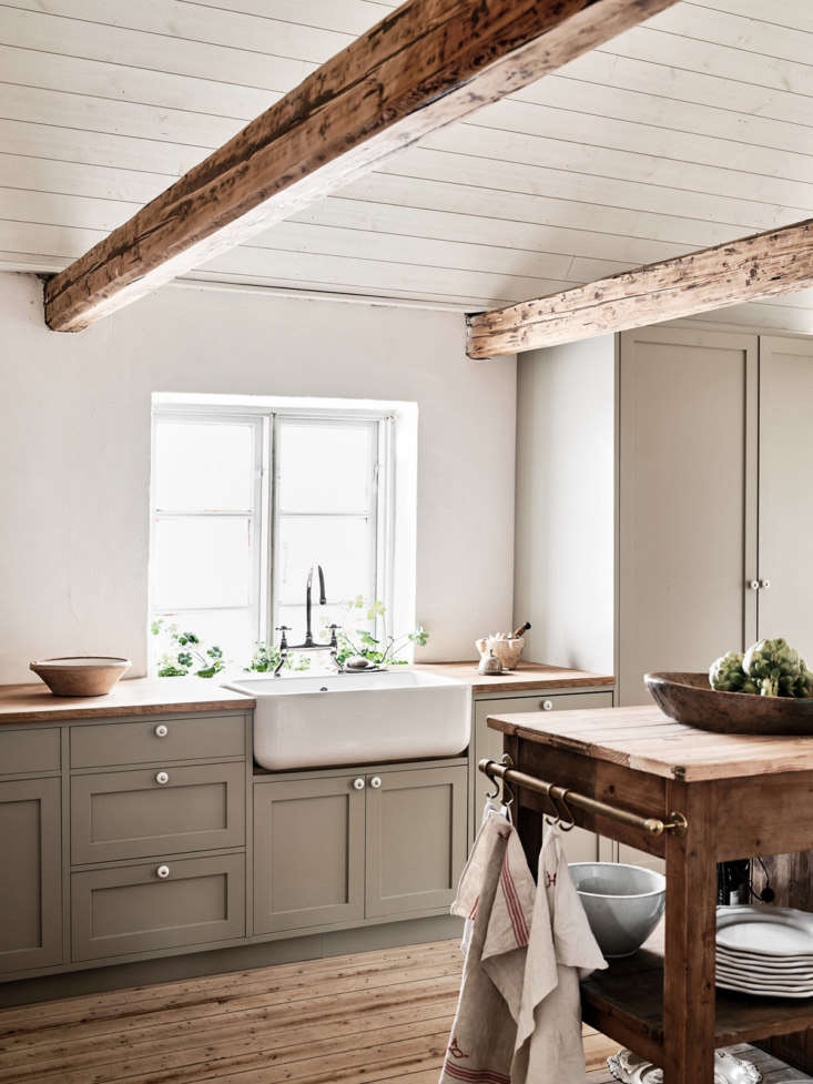 The sink is a Shaws Original and the faucet came from Sekelskifte (see others like it in  Easy Pieces: Traditional Bridge Faucets). The fridge and freezer are concealed in the tall cupboard.