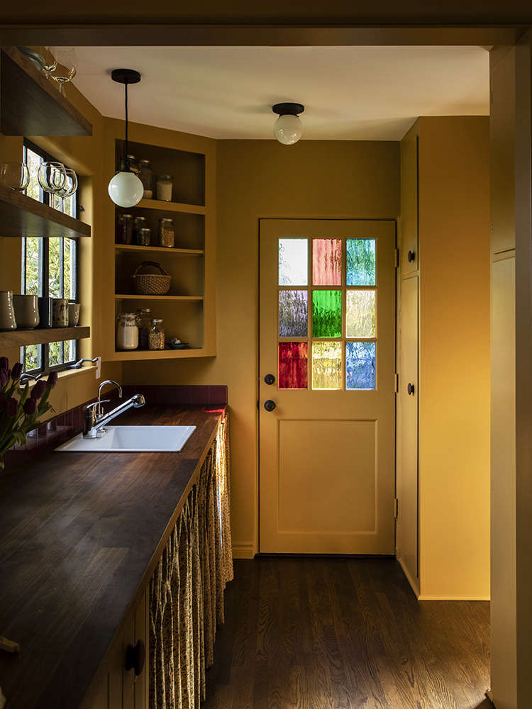 A coffee and pantry area is just beyond the kitchen. The skirted sink lends some vintage charm.