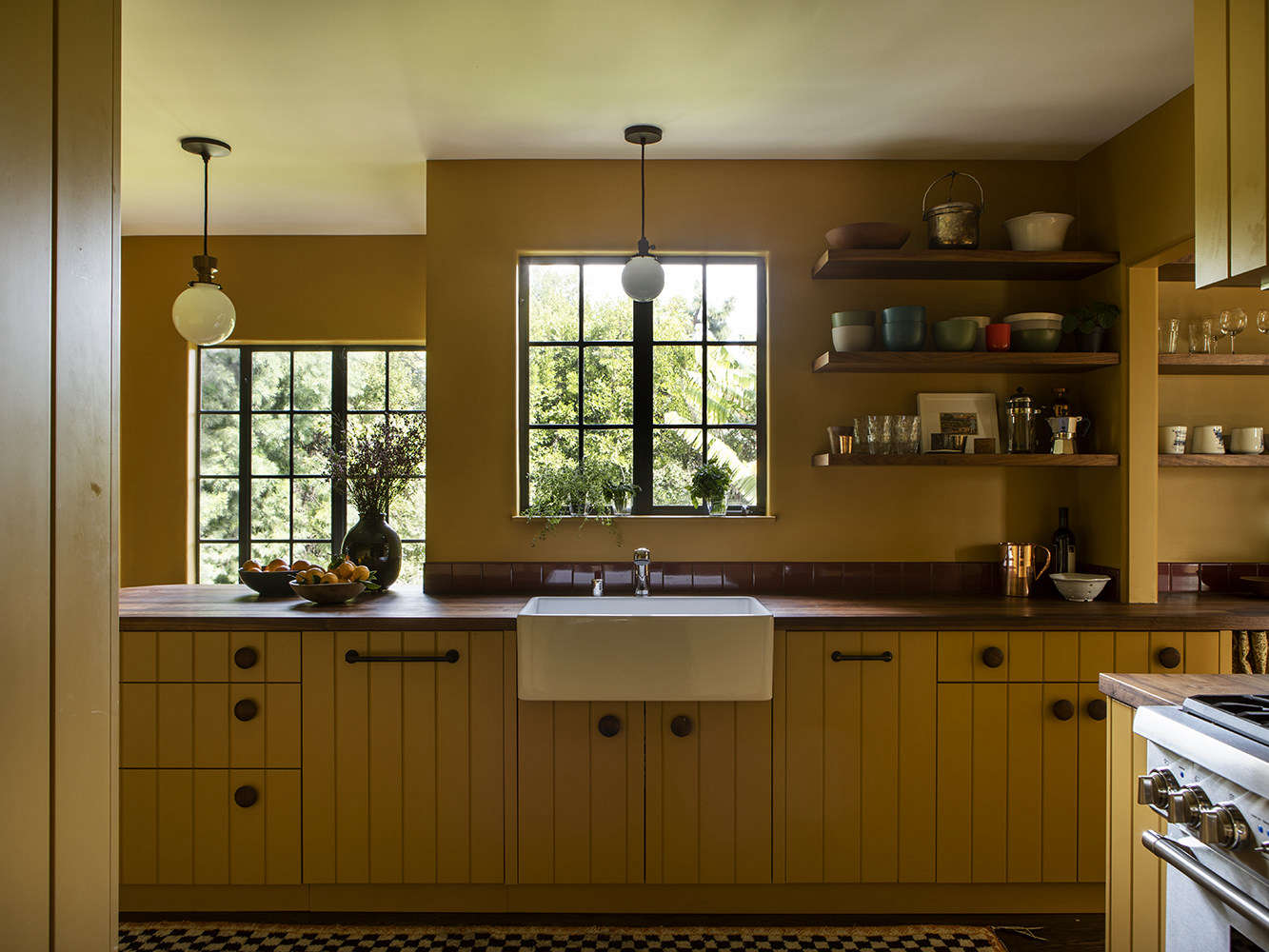 Oversized wood drawer knobs from Nice Knobs add personality, as does the open shelving, which allows the couple to display art and some of their more unique kitchen items. A single row of Interceramic tiles (in Wineberry) forms the backsplash.