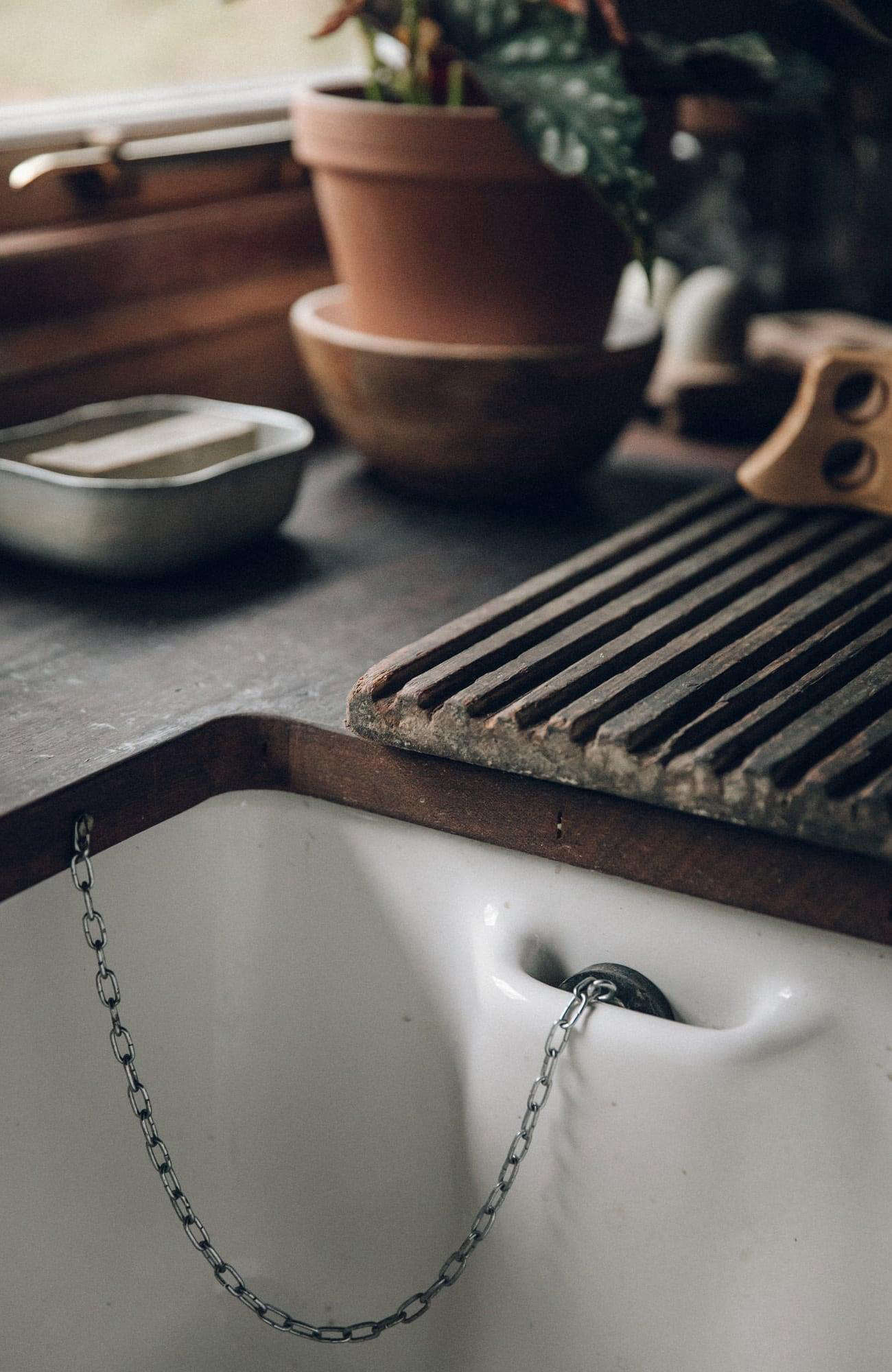 The early 00s ceramic sink is detailed with a stopper pocket.