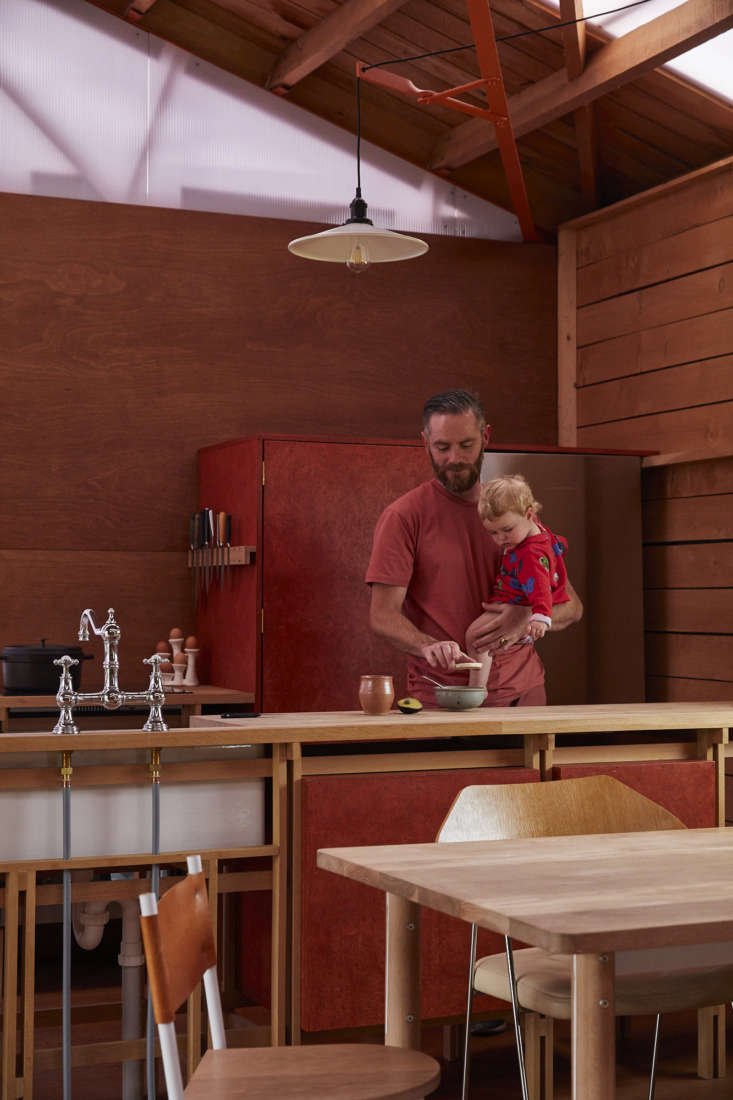 The pantry cupboard and fridge are enclosed in stained strand board. The horizontal wall paneling was milled from a macrocarpa tree that came down in a nearby storm: &#8