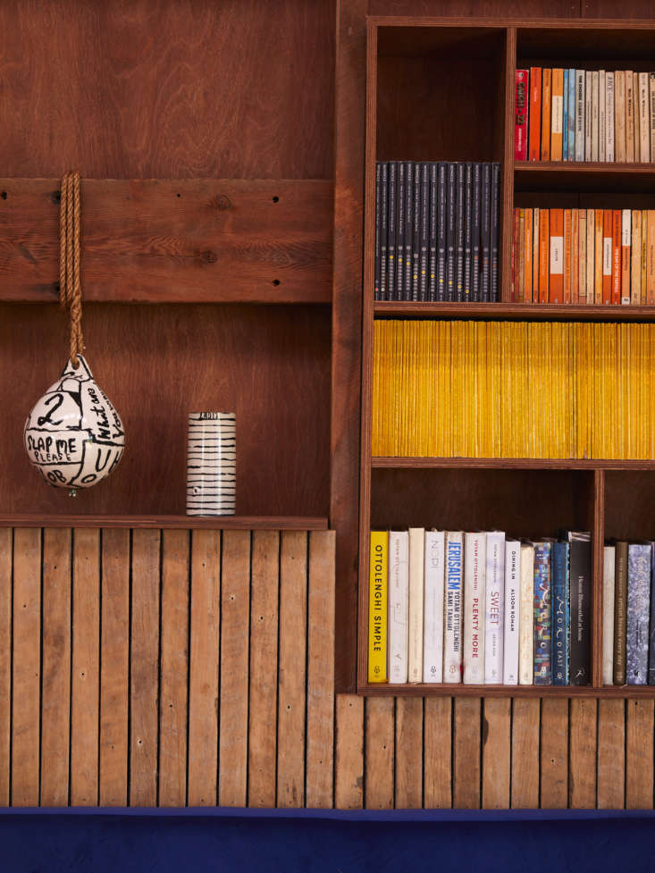 A ceramic ball by artist Martin Poppelwell hangs between the bookshelves. Ben used the old flooring to make the slatted paneling.