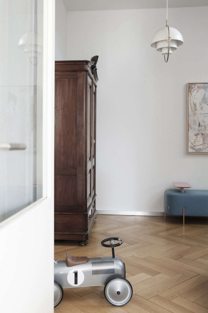An Updated Neoclassical House for a Modern Minimalist Family &#8\2\20;In the hallway, we opted for a combination of antiques and very modern, aesthetically simple furnishings,&#8\2\2\1; says Lea. The cupboard, a family heirloom, overlooks Sencal&#8\2\17;s Elephant bench on the herringbone floor. The Gubi Multi Lite is part of a collection of sculptural contemporary white lights that Studio Oink introduced throughout.