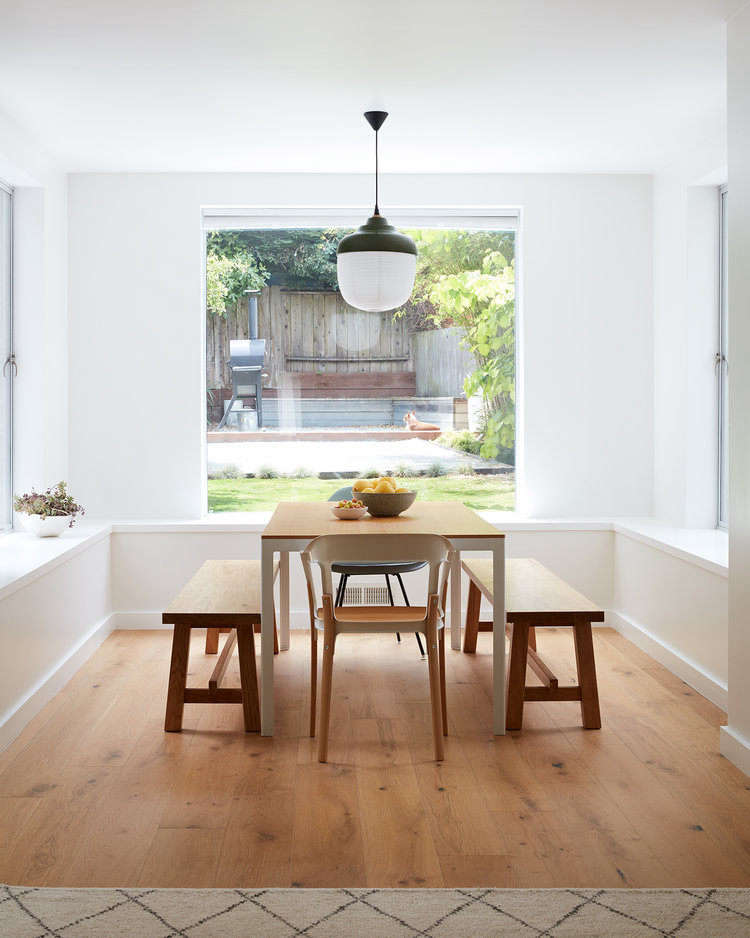 Hanging above the Luciano Bertocini dining table is the piece that inspired their remodel: the New Old Light by Taiwanese lighting company Kimu. The benches are from Ikea.