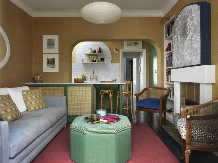The kitchen is tucked in the other end of the room, set off by a marble-topped breakfast bar faced with rattan (which in the corner cleverly serves as a ventilated radiator cover). The arched wall was &#8