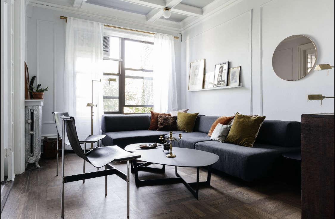 Delia mixes new and vintage pieces in the living room. A West Elm sectional plays nice with two vintage leather chairs handed down from the client&#8