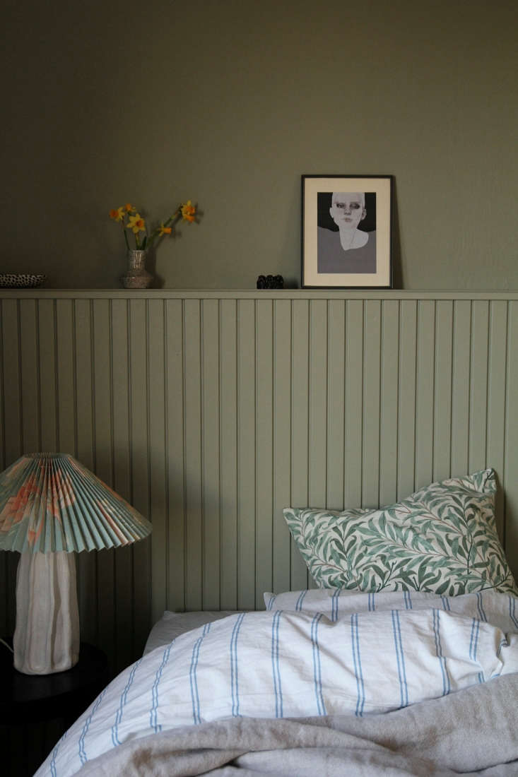 DIY Paneled Wood Headboard A Finnish Bloggers Clever Bedroom Upgrade Maiju made the bedside ceramic lamp at a clay workshop and finished it with a vintage pleated shade. The leaf pillow is made from a William Morris fabric bought on Etsy; the striped bedding is from H&M Home.