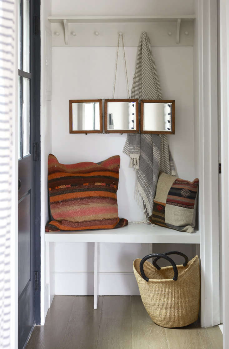 The private entrance on the side of the structure opens to a compact mudroom with a built-in bench and combination shelf and hanging rack—&#8