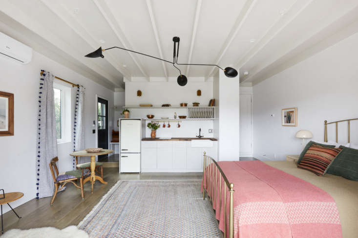 In place of two cars, the approximately 400 square foot space has a kitchen, eating area, and bed. The flooring is engineered European oak. The walls are painted Farrow & Ball&#8