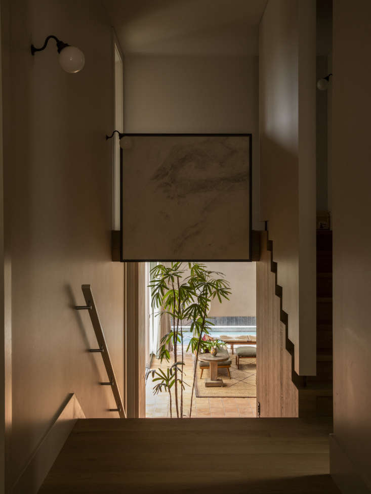 Collective Composition A Historic Villa Renovation in Auckland by Katie Lockhart and Jack McKinney Architects A custom staircase, designed as if floating, is rendered in natural oak with walls in Aalto Illusion colored plaster, also from Resene Rockcote. Above the stairwell is a piece of the same marble featured in the kitchen, Biello marble, encased in a metal frame. The wall lights on the left are the PR00\2 Bracket Lights from Apologia in Japan.