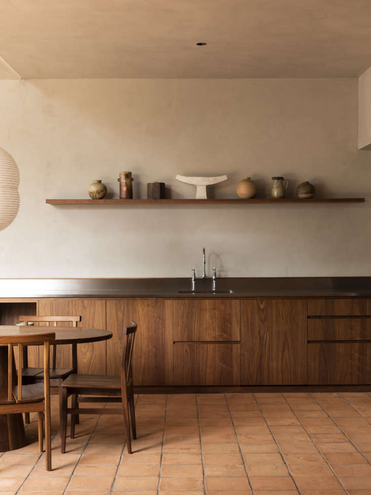 On a single floating shelf above the kitchen sink sits a selection of vintage Japanese ceramics and other pieces from New Zealand potters Bruce and Estelle Martin, sourced by Lockhart. The tiles throughout the room are Italian terracotta tiles from Fornace Brioni. The walnut table and chairs are custom by Grant Bailey.