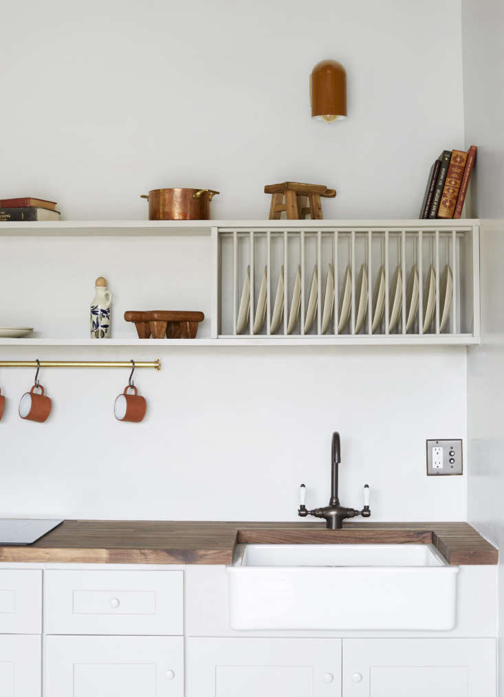The kitchen has a walnut butcher block counter from Floor & Decor, and an Ikea apron-front sink with a Rohl faucet. Shanty had her carpenter install the wooden plate rack between two shelves, painted like the cabinets in a Farrow & Ball white.