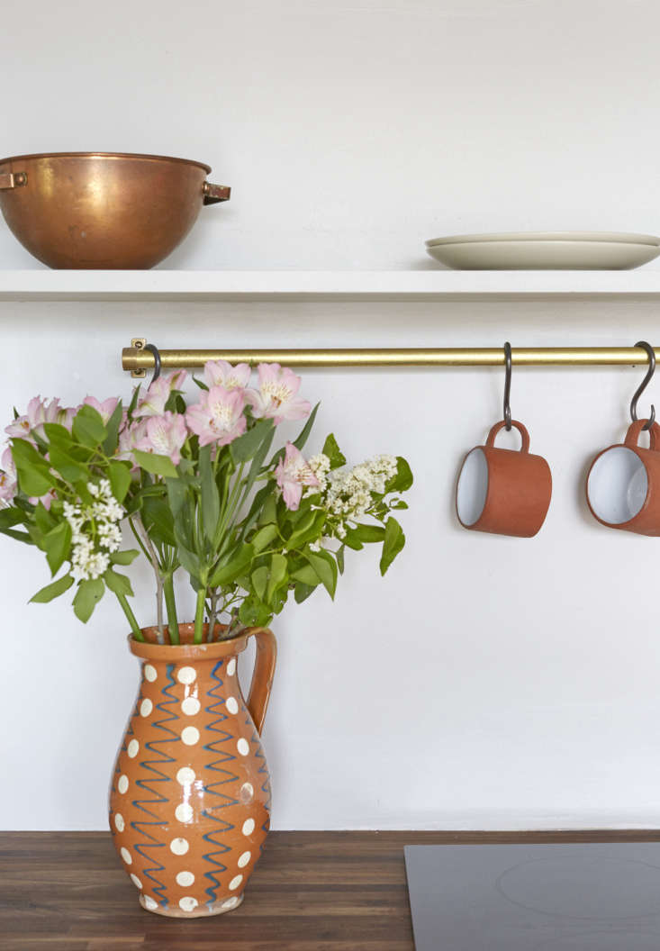 Mugs hang on S hooks from a brass kitchen rail. See more in Trend Alert:  Kitchens with Utensil Rails.