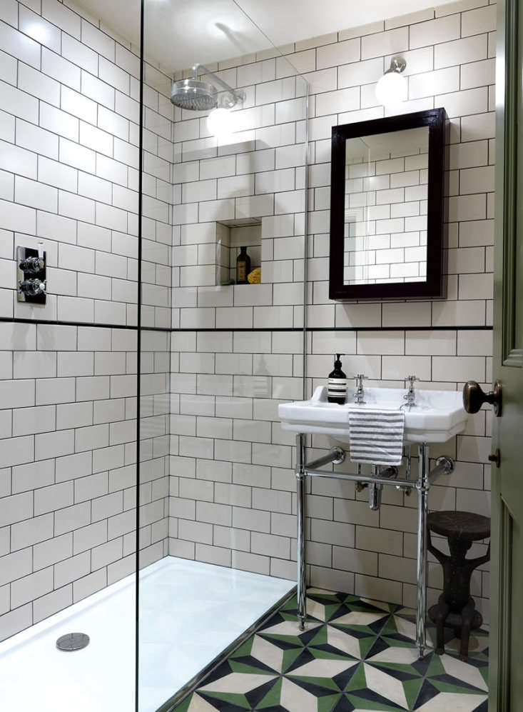 In the tiny bath, Lonika installed a glass-walled shower with metro tiles on the walls and Portuguese Encaustic Alvito tiles on the floor, both from Fired Earth. The cabinet is bespoke and painted in a glossy Farrow & Ball shade of auberine called Brinjal.