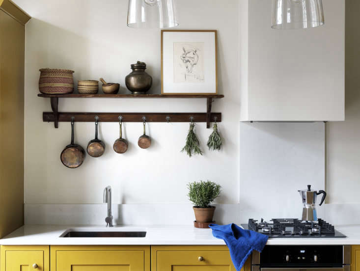 An antique shelf provides storage and a place to prop art over the sink. The unlacquered brass cabinet knobs are from Rowen & Wren, and the Old School Electric Blown Glass Pendant Lights are from Holloways of Ludlow.
