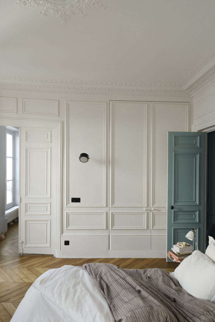 The architects made up for a lack of closets by building in a wall of cabinets with paneled moldings to work with the original plasterwork on the ceiling.