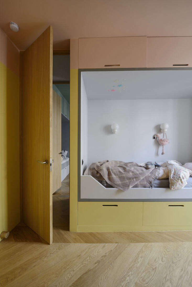 The kids are two and four, and have side-by-side rooms, each with a custom alcove bed painted in its own color-blocked palette—the architects call this one Strawberry and Vanilla. (They used paints from Farrow & Ball and French company Argile throughout.) Note the built-in storage below and above the beds.