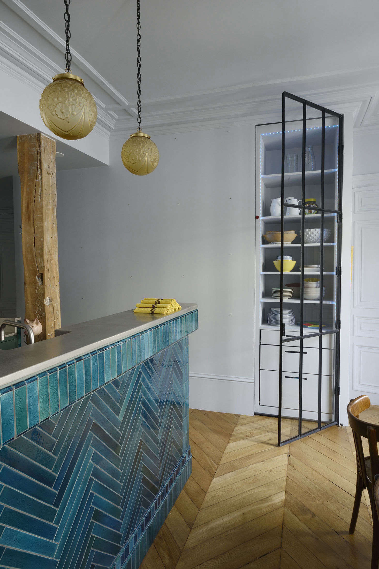 Ab0ve: A built-inn pantry with a glazed steel door stands on the other side of the kitchen bar. The clients bought the French glass hanging lights at a flea market.
