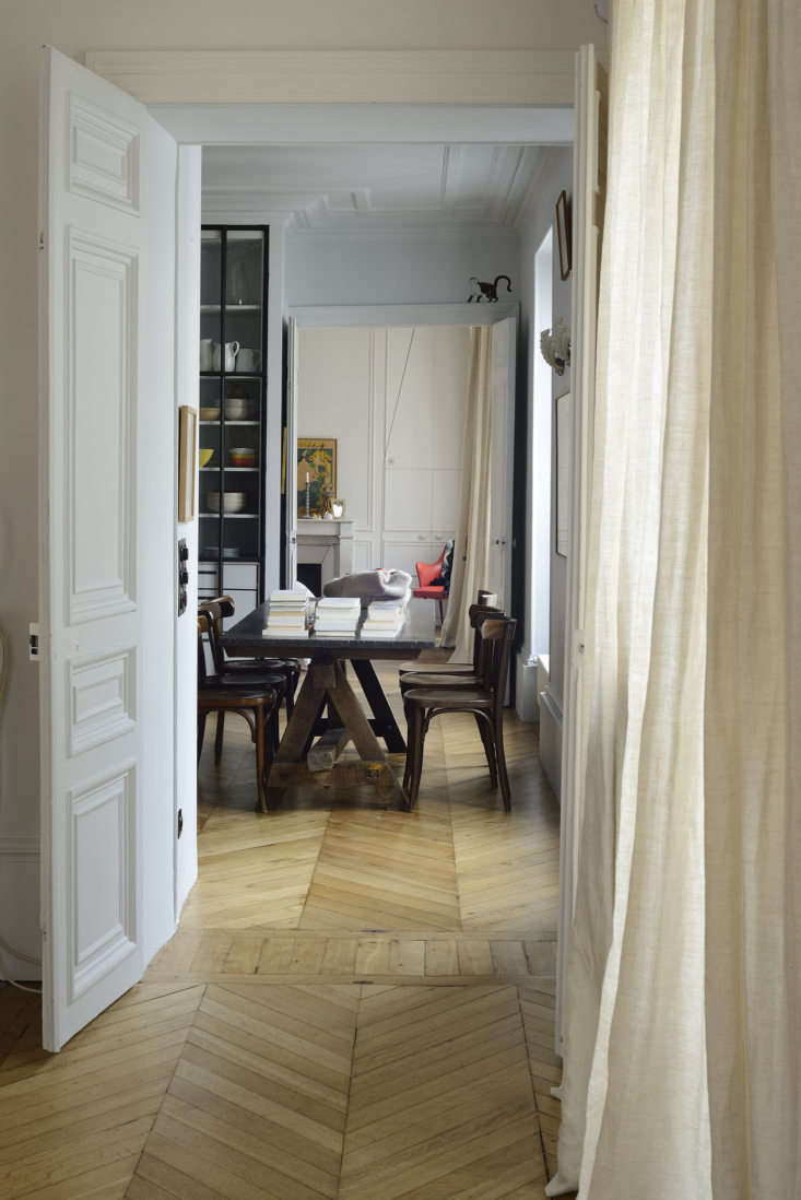 The dining table doubles as a work area. It was bought at a Paris flea market and has a top made of blue stone from Liège.