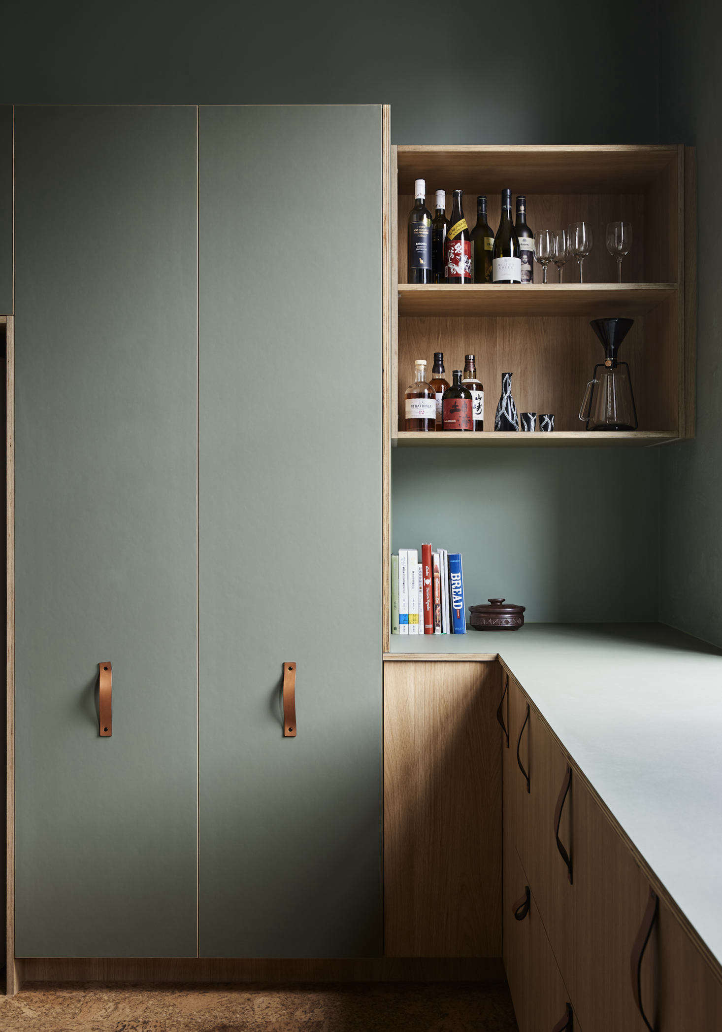 The kitchen cabinets were custom-made by MTR Designer Cabinets using Laminex boards in Elegant Natural Oak finish. The pantry features doors fronted with with green panels of furniture linoleum by Forbo. The same linoleum was used to top the -mm birch plywood countertop as well.